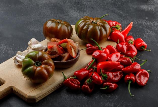 Tomates kumato con rodajas, pimientos rojos, bulbos de ajo en la pared gris y tabla de cortar, vista de ángulo alto.