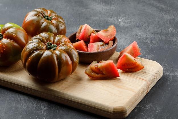Tomates kumato con rodajas en placa en el grunge y la pared de la tabla de cortar, vista de ángulo alto.