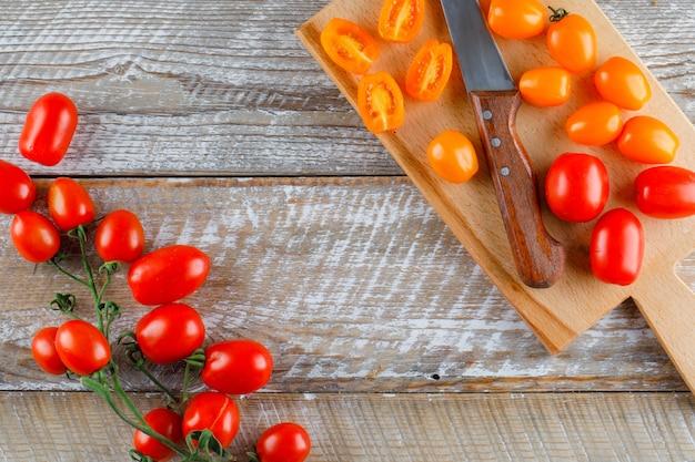 Tomates maduros con cuchillo plano en madera y tabla de cortar