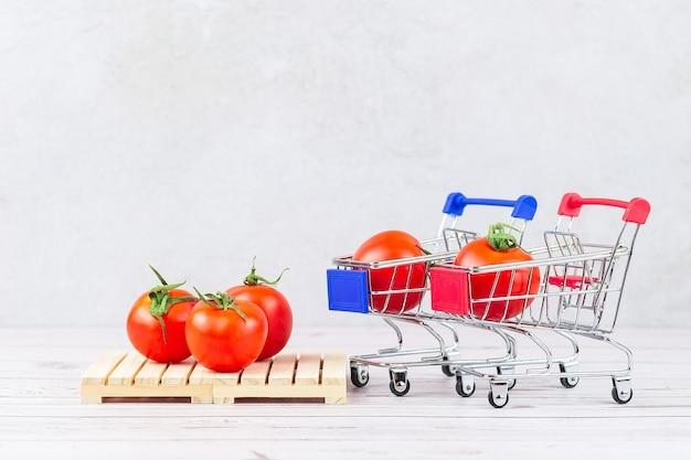 Tomates maduros frescos en un carrito de la compra y en un palet, concepto de almacén