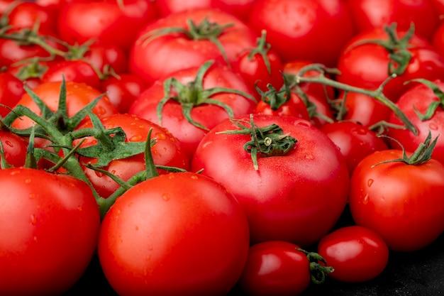 Tomates maduros con gotas de agua como vista lateral de fondo