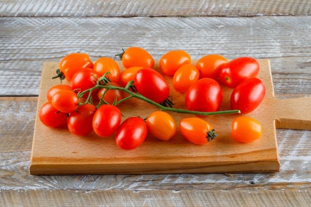 Tomates maduros en madera y tabla de cortar.