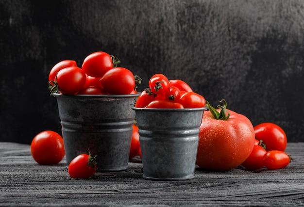 Tomates en mini cubos en madera gris y pared sucia. vista lateral.