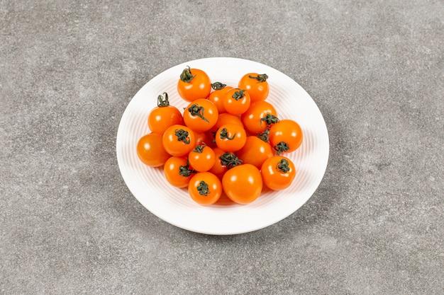 Tomates naturales en plato, sobre el mármol.