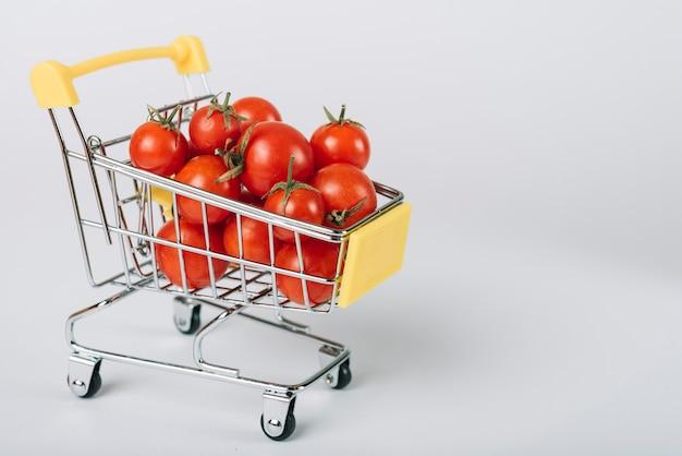 Tomates orgánicos frescos en carretilla en el contexto blanco