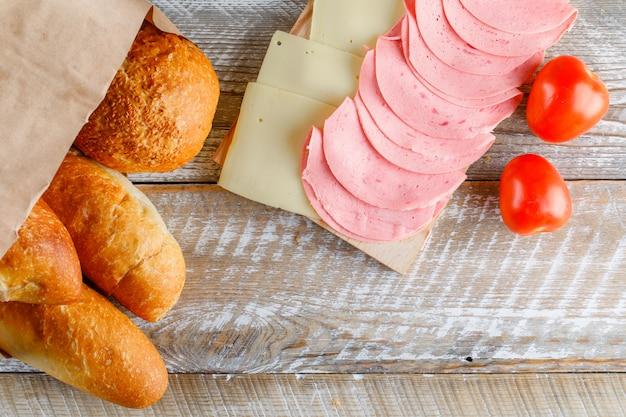 Tomates con pan, queso, salchichas en mesa de madera, endecha plana.