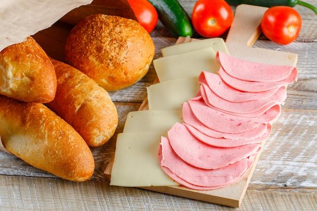 Tomates con pan, queso, salchichas, pepinos en mesa de madera, vista de ángulo alto.
