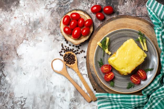 Tomates de pan con queso de vista superior en placa en tablero de madera tomates cherry en tablero de madera cucharas de madera en nude