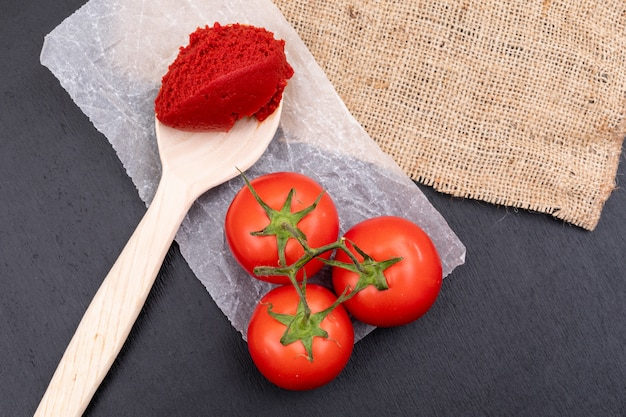 Tomates en pasta de tomate de polietileno en una cuchara de madera cerca de la tela de saco sobre superficie de piedra negra