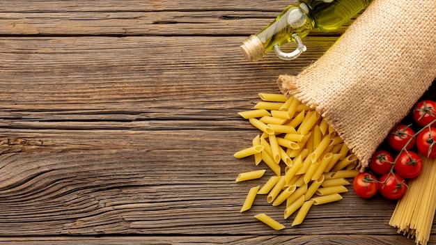 Tomates penne crudos y aceite de oliva en la mesa de madera con espacio de copia