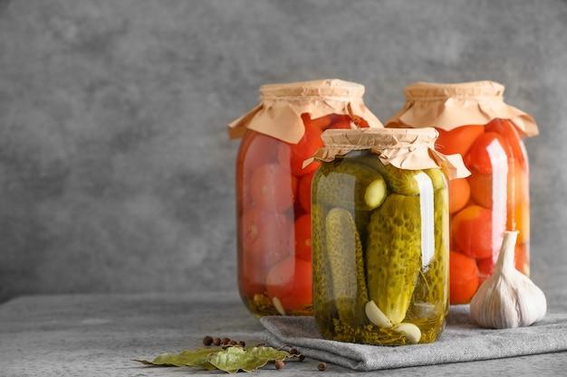 Tomates y pepinos encurtidos caseros en frascos de vidrio en el espacio de copia de mesa gris