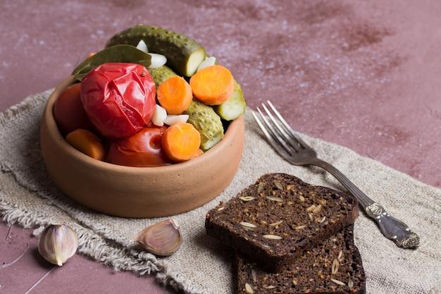 Tomates y pepinos en escabeche en cerámica, con pan de centeno