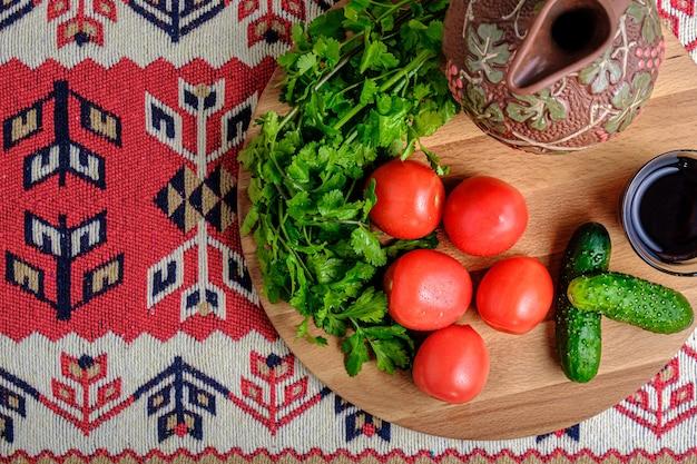 Tomates, pepinos, hierbas, una jarra y vino en una bandeja de madera.