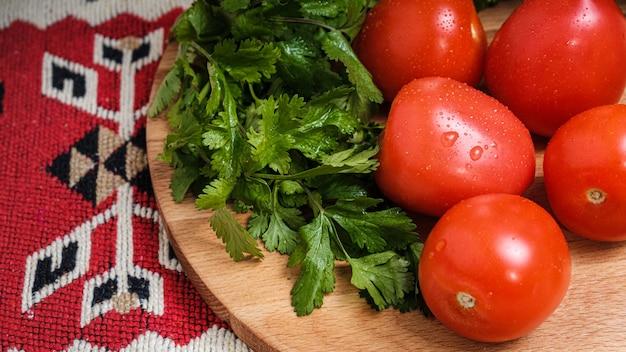 Tomates, pepinos y hierbas sobre una tabla para cortar.