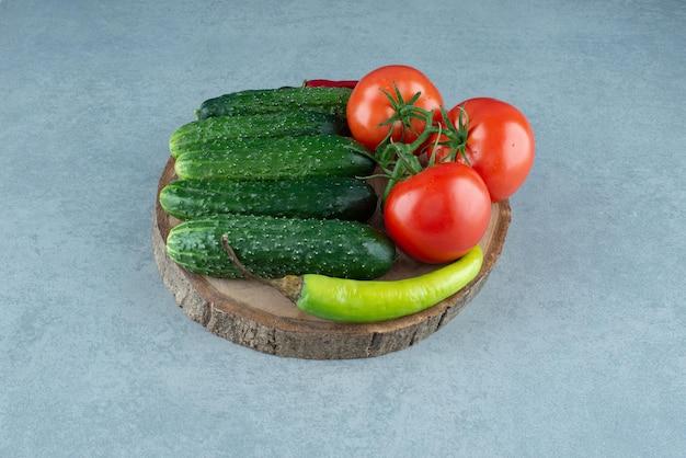 Tomates, pepinos y pimiento en pieza de madera.