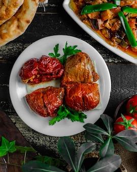 Tomates y pimientos rellenos sobre la mesa