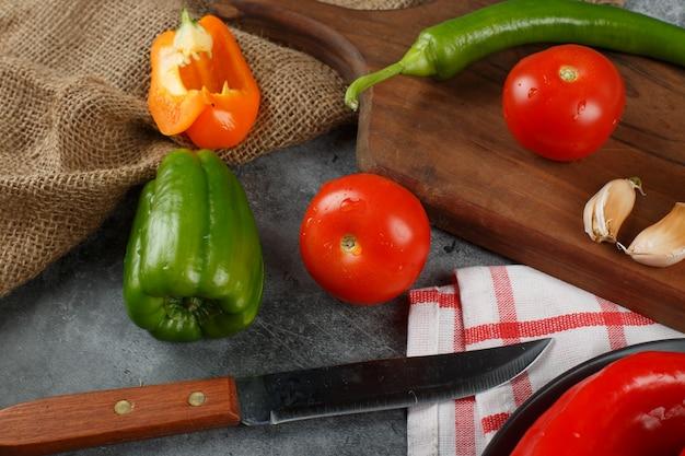 Tomates y pimientos verdes con un cuchillo. vista superior.