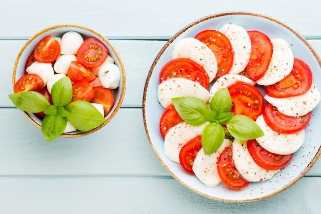 Tomates, queso mozzarella, albahaca y especias en pizarra de piedra pizarra gris. ingredientes de la ensalada caprese tradicional italiana. comida mediterránea.