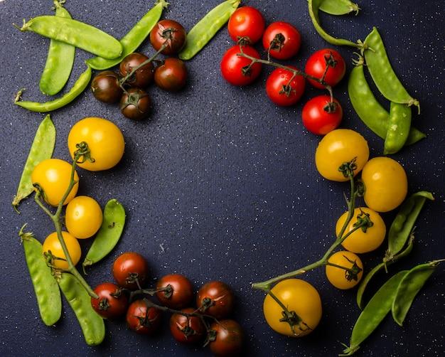Tomates rojos y amarillos y guisantes verdes.