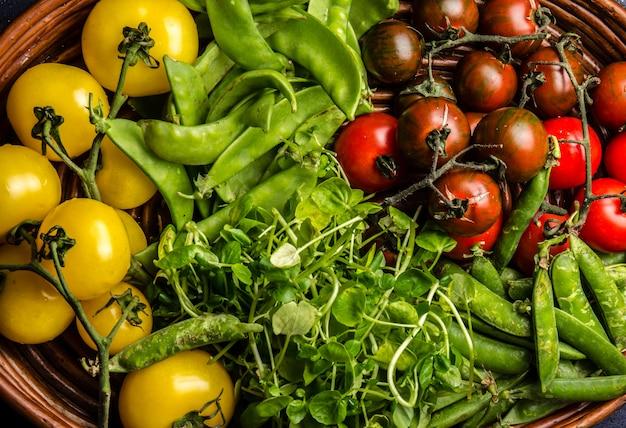 Tomates rojos y amarillos sobre paté negro de hierro fundido y guisante verde sobre negro