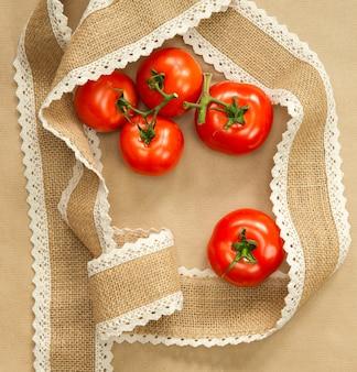 Tomates rojos en artesanía marrón con cinta de arpillera