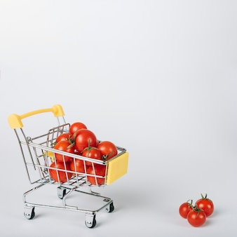 Tomates rojos frescos en carretilla en el fondo blanco
