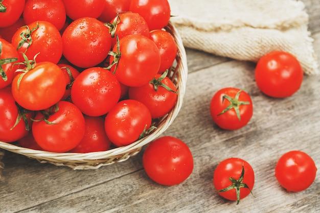 Tomates rojos frescos en una cesta de mimbre en una vieja mesa de madera. maduros y jugosos tomates cherry con gotas de humedad, mesa de madera gris, alrededor de un paño de arpillera. en un estilo rústico.