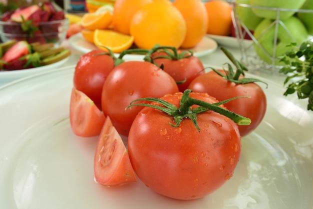 Tomates rojos frescos con gotas de agua sobre la piel del tomate. mezclar frutas. frutas frescas cerca de ti.