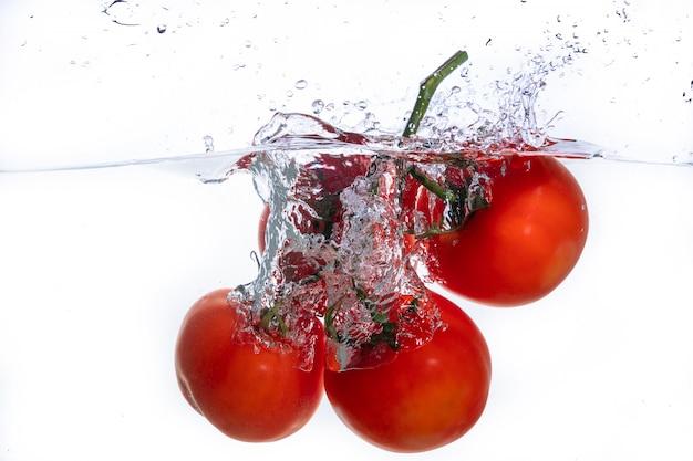 Tomates rojos frescos en salpicaduras de agua aislado