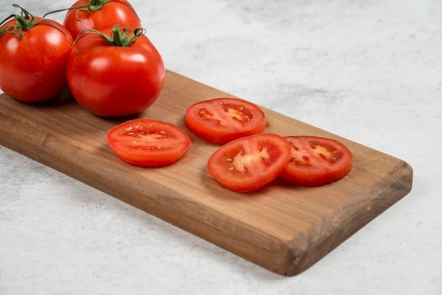 Tomates rojos frescos sobre una tabla de cortar de madera