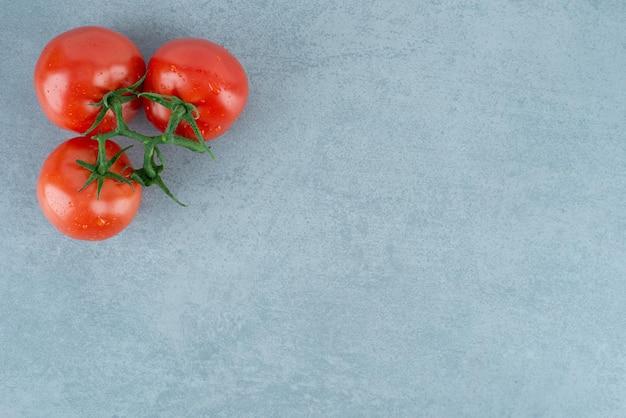 Tomates rojos con gotas de agua en azul.