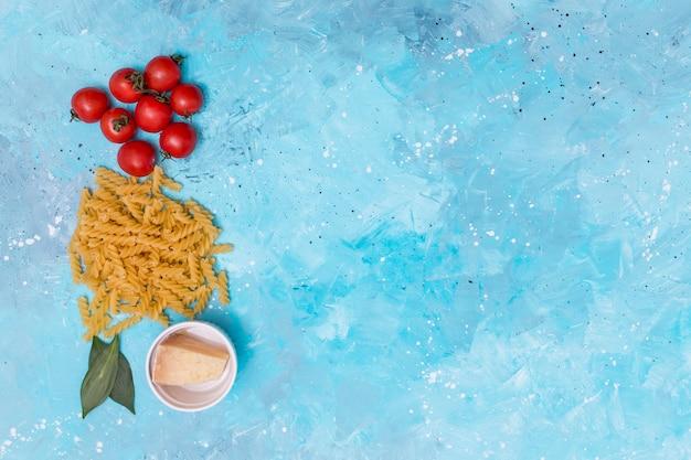 Tomates rojos; pasta fusilli cruda retorcida; laurel y queso sobre fondo azul