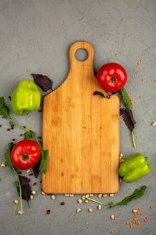 Tomates rojos pimientos maduros y verdes frescos junto con hierbas en un escritorio ligero