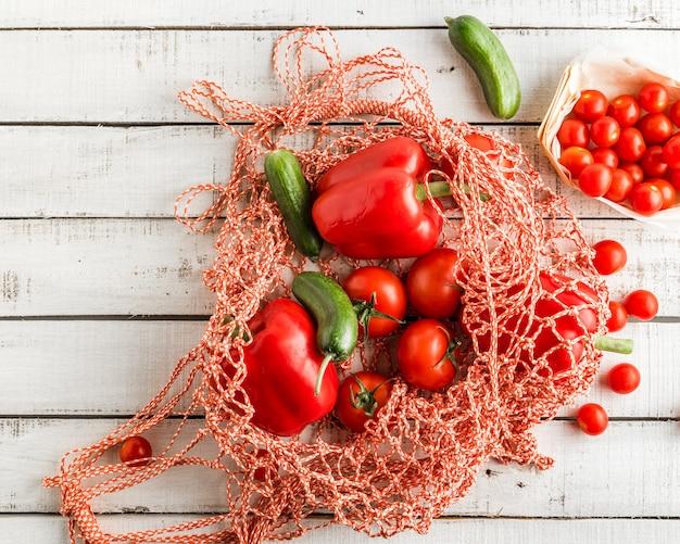Tomates rojos y pimientos, pepinos en una bolsa de cadena sobre fondo blanco rústico