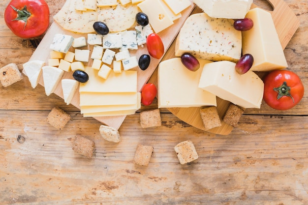 Tomates rojos, uvas, aceitunas y bloques de queso en el escritorio de madera