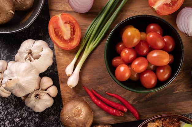 Los tomates en la taza negra con cebolletas, pimientos, tomates y cebollas rojas.