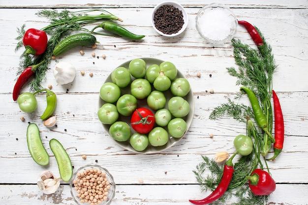 Tomates verdes, encurtidos en mesa de madera blanca con pimientos verdes y rojos y chiles, hinojo, sal, pimienta negra, ajo, guisantes, primer plano, concepto saludable, vista superior, endecha plana