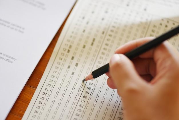 Tome el examen final estudiante de secundaria con lápiz escrito en hoja de respuestas en papel.