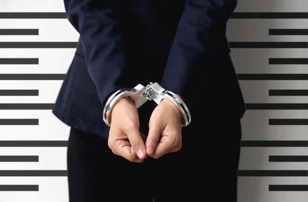 Tome una foto de un criminal en la recopilación de datos con esposas con un metro de línea de patrón alto