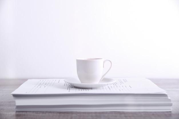 Tómese un descanso beber café concepto. taza de café sobre una pila de papel sobre la mesa