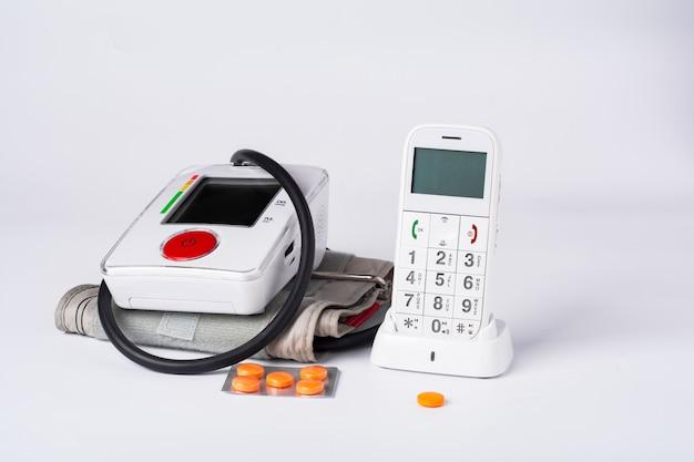 Tonómetro electrónico blanco con teléfono y tabletas.