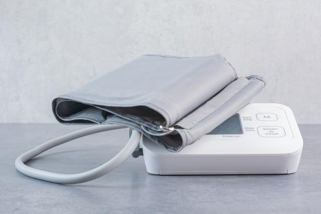Tonómetro electrónico médico sobre mesa de mármol.