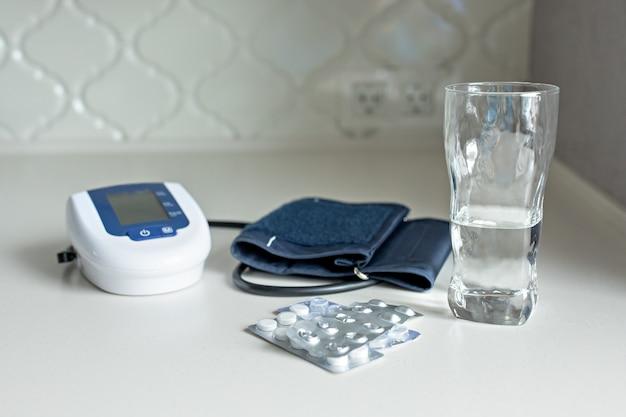 Tonómetro electrónico, pastillas y un vaso de agua sobre una mesa blanca