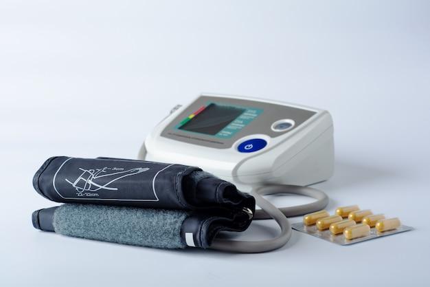 Tonómetro electrónico sobre un fondo blanco con pastillas