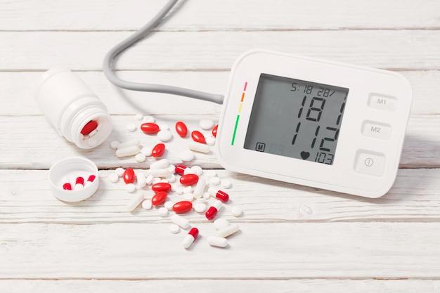 Tonómetro moderno con pastillas en la mesa de madera
