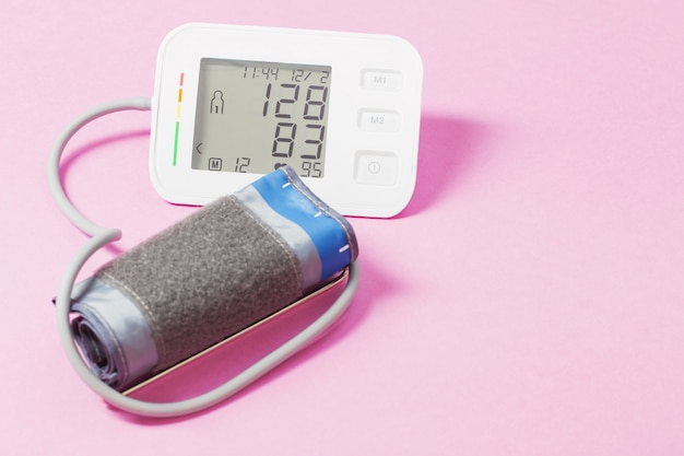 Tonómetro moderno en superficie rosa