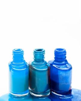 Tonos azules de esmalte de uñas se derramaron alrededor de tres botellas abiertas