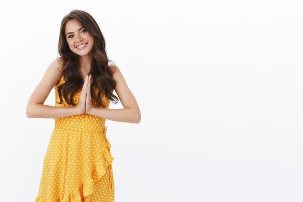 Tonto, tierna y hermosa mujer con vestido amarillo, tomarse de las manos juntas en oración, agradeciendo por la ayuda, sonriendo alegre, inclinando la cabeza y mirando agradecida, de pie en la pared blanca feliz y pacífica, namaste