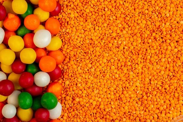 Top caramelos de colores en lentejas rojas crudas