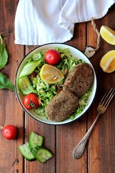 Top chuleta de ternera con ensalada de vegetales frescos en un recipiente de metal